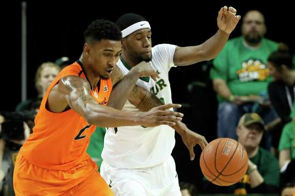 Oklahoma State guard Le'Bryan Nash, left, and Baylor's Royce O'Neale chase after a loose ball in the first half of an NCAA college basketball game Monday, Feb. 9, 2015, in Waco, Texas. (AP Photo/Tony Gutierrez)