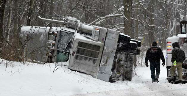 A tractor trailer lies on its side on River Road Monday morning, Feb. 9, 2015, in Bethlehem, N.Y.  The truck was carrying a load of road salt that flowed into the woods on the side of the road. (Skip Dickstein/Times Union) Photo: SKIP DICKSTEIN