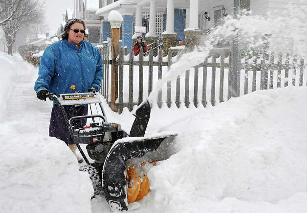 Debra McCormick uses a snow blower to clear the sidewalk in front of her house during a snowstorm on Monday afternoon, Feb. 9, 2015, in Troy, N.Y. McCormick's grandson Alex Hebert, 13, shovels the front sidewalk and porch area in the background. (Lori Van Buren / Times Union) Photo: Lori Van Buren / 00030522A