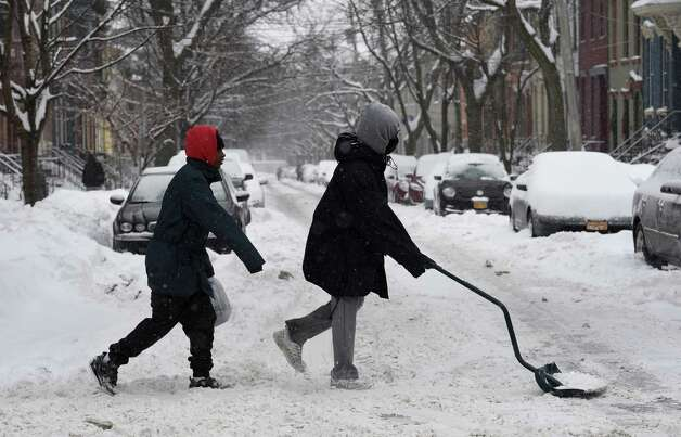 Xavier Perez, 14, right tries to get some business shoveling snow on Lark Street Monday afternoon Feb. 9, 2015 in Albany, N.Y.        (Skip Dickstein/Times Union) Photo: SKIP DICKSTEIN