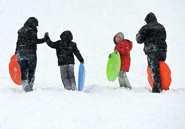 Sledders walk back up the hill in Frear Park on Monday afternoon, Feb. 9, 2015, during a snowstorm in Troy, N.Y. (Lori Van Buren / Times Union) Photo: Lori Van Buren / 00030522A