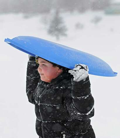 Ebarister LeBron, 7, of Troy carries his sled on his head as he climbs a hill in Frear Park Monday afternoon, Feb. 9, 2015, during a snow storm in Troy, N.Y. (Lori Van Buren / Times Union) Photo: Lori Van Buren / 00030522A
