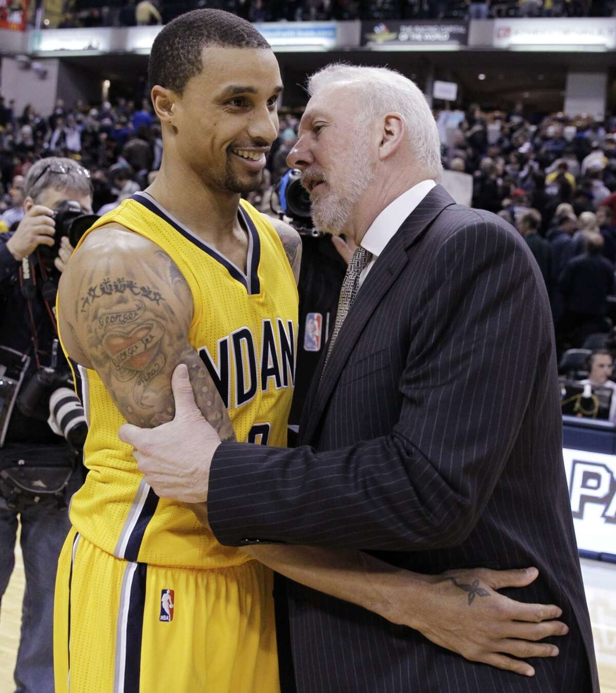 Indiana Pacers' George Hill (3) congratulates San Antonio Spurs head coach Gregg Popovich following an NBA basketball game Monday, Feb. 9, 2015, in Indianapolis. San Antonio won the game 95-93. With the win Popvicch joined the 1000-win club.(AP Photo/Darron Cummings)
