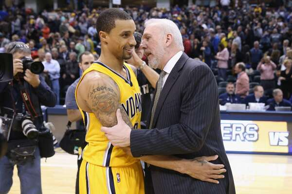 Gregg Popovich the head coach of the San Antonio Spurs talks to a former player George Hill #3 of the Pacers after earning his 1,000th career for his NBA career tonight against the Indiana Pacers at Bankers Life Fieldhouse on February 9, 2015 in Indianapolis, Indiana.