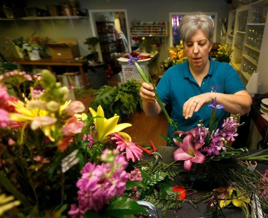 1.La diseñadora Michelle Brooks, de Elaine's Florist & Gift Baskets, compone un arreglo floral. Esta semana es la más ocupada para esa florería. Photo: Karen Warren, Houston Chronicle