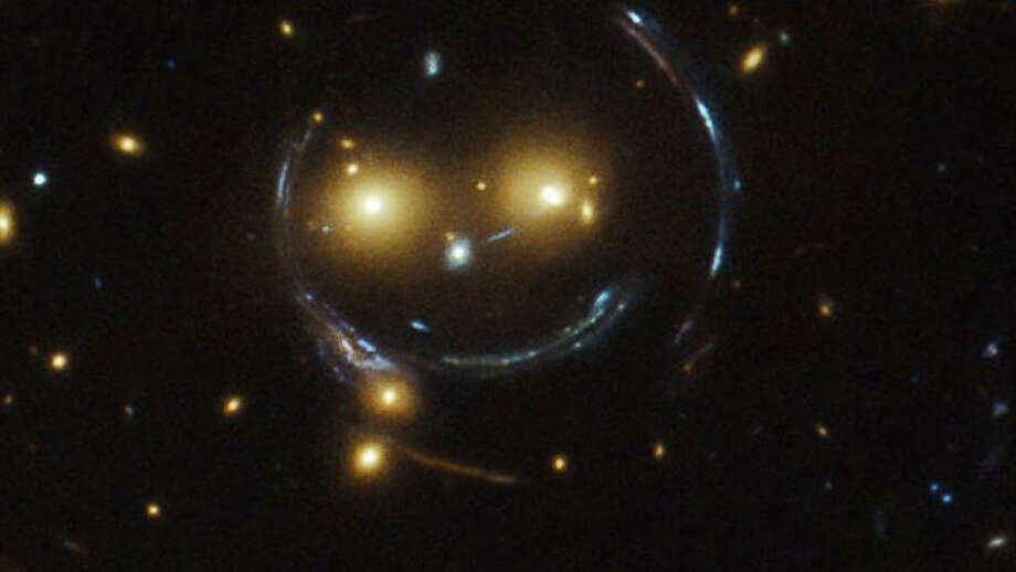 GREETINGS, EARTHLINGS! OUR INVASION FORCE HAS JUST ENTERED YOUR SOLAR SYSTEM:A new NASA Hubble Telescope image shows the galaxy cluster SDSS J1038+4849 smiling for the camera. Photo: NASA/ESA