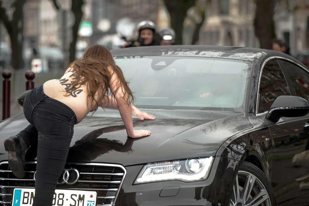 """PIMP MY RIDE: A Femen activist jumps on a car carrying former IMF chief Dominique Strauss-Kahn as he arrives for his trial in Lille, France. She was joined by two other topless women hurling insults at Strauss-Kahn, who has been charged with """"aggravated pimping."""" All three were hauled away by police."""