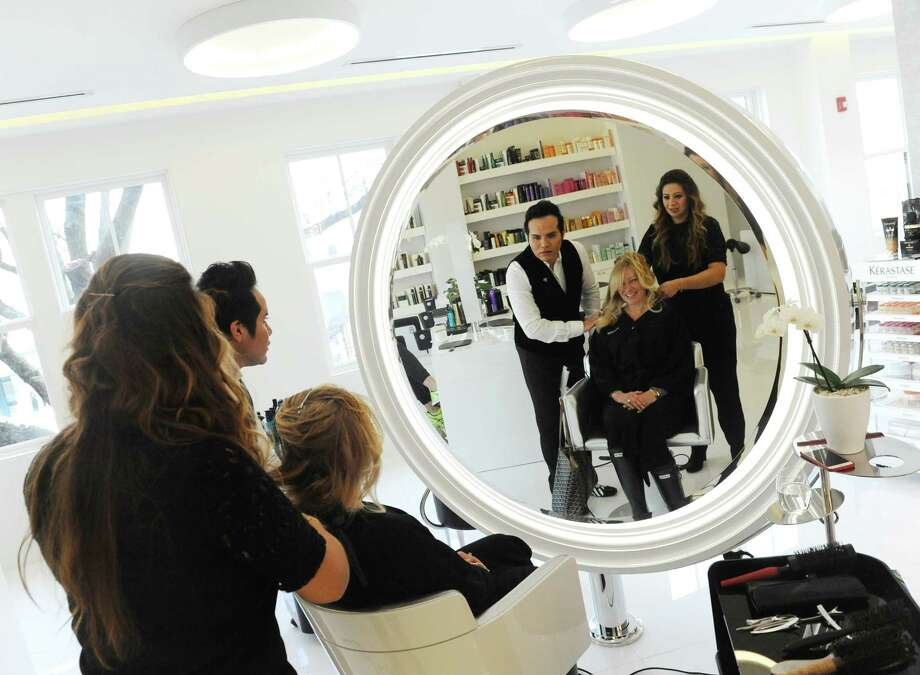 Rowayton, Conn., resident Jeanne Barnett gets her hair styled in a Paris blow dry by salon owner Becker Chicaiza and Eliana Maillard while sitting in the signature diva chair at Becker Salon in downtown Greenwich, Conn. Tuesday, Feb. 10, 2015.  Becker Salon, owned by Becker Chicaiza, offers a variety of services in its second-floor space overlooking Greenwich Avenue.  Throughout February, the salon is offering new clients a complimentary consultation and blow dry. Photo: Tyler Sizemore / Greenwich Time