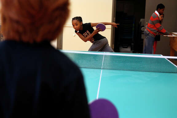 Lemya Richardson, 10, returns a shot while playing pingpong with Aiden Beaupian, 9, at the Boys & Girls Club.