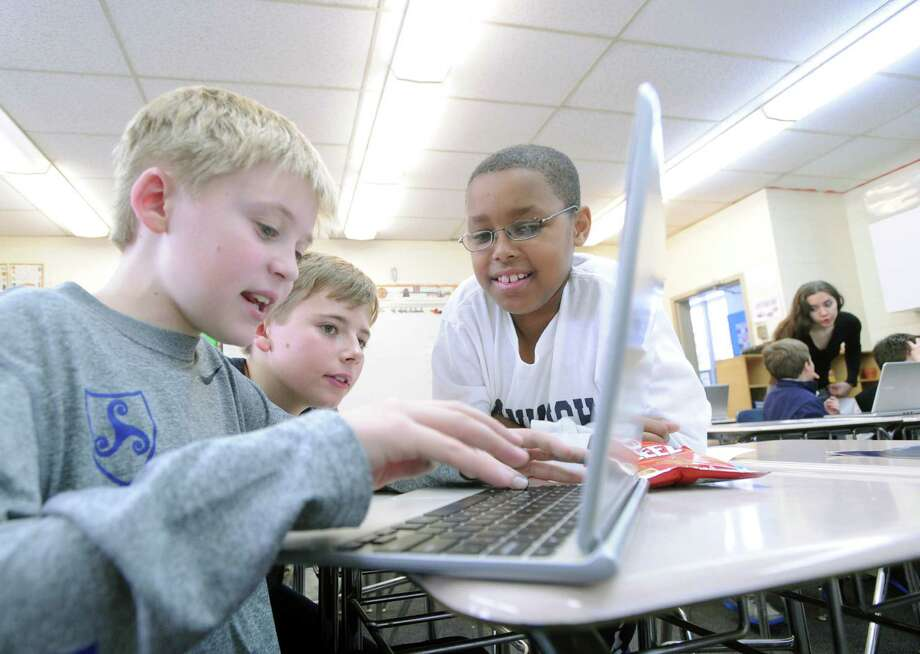 From left, Stanwich School students, Jameson Gerson, 11, Kaleb Root, 12, and William Plummer, 10, use a computer to create an app that will serve as a guide to the popular Minecraft game during the Level Up class that is part of an after-school activity at the Stanwich School in Greenwich, Conn., Tuesday afternoon, Feb. 10, 2015. The students are part of a project in which they are collaborating with fellow students in India. Photo: Bob Luckey / Greenwich Time
