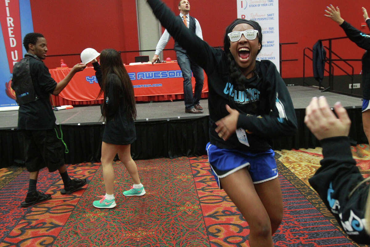 Motivational speaker Aric Bostick (on stage, background) leads high school students during a pep session at the fourth annual Confluence summit held by San Antonio Water System at the Henry B. Gonzalez Convention Center. This year's event focused on water quality and informed more than 800 students from public and private area high schools about the utility's water service.