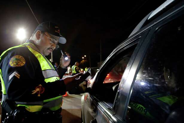 In this Thursday, Jan. 29, 2015 photo, Miami police officer Luis Ortiz looks at a driver's license he requested from a motorist during a drunk-driving checkpoint in Miami. A South Florida DUI attorney contends the commonly-used checkpoints violate driver's constitutional rights. (AP Photo/Lynne Sladky)