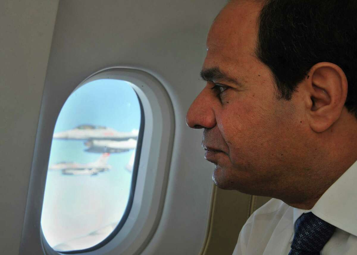 FILE - In this Sept. 26, 2014 file photo provided by Egypt's state news agency MENA, Egyptian President Abdel-Fattah el-Sissi looks out as air force jets escort the presidential airplane after it entered Egyptian airspace. El-Sissi scrambled to avert any damage to ties with Arab Gulf countries after he and his aides were allegedly caught on audiotape mocking his crucial oil-rich allies and discussing how to milk them for billions. El-Sissi's phone calls to leaders of Saudi Arabia, Kuwait and the United Arab Emirates on Monday, Feb. 9, 2015, reflected the pivotal role of financial aid from those nations. (AP Photo/MENA, File)