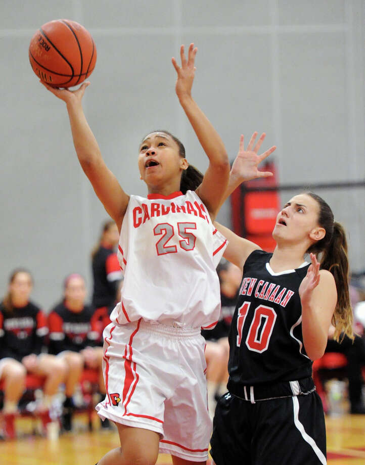 At left, Jayla Faison (#25) of Greenwich scores on a layup as she gets past Marina Braccio (#10) of New Canaan during the girls high school basketball game between Greenwich High School and New Canaan High School at Greenwich, Conn., Tuesday, Feb. 10, 2015. Photo: Bob Luckey / Greenwich Time