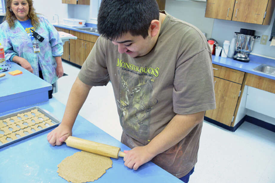 Nicholas Rodriguez, center, a student at Harlandale ISD's Jewel Wietzel Center, rolls out dough for dog biscuits as teacher Ruby Aguirre looks on. The treats are a fundraiser for the students at the center. Photo: Courtesy / Harlandale ISD / Harlandale ISD    San Antonio, TX   www.harlandale.net