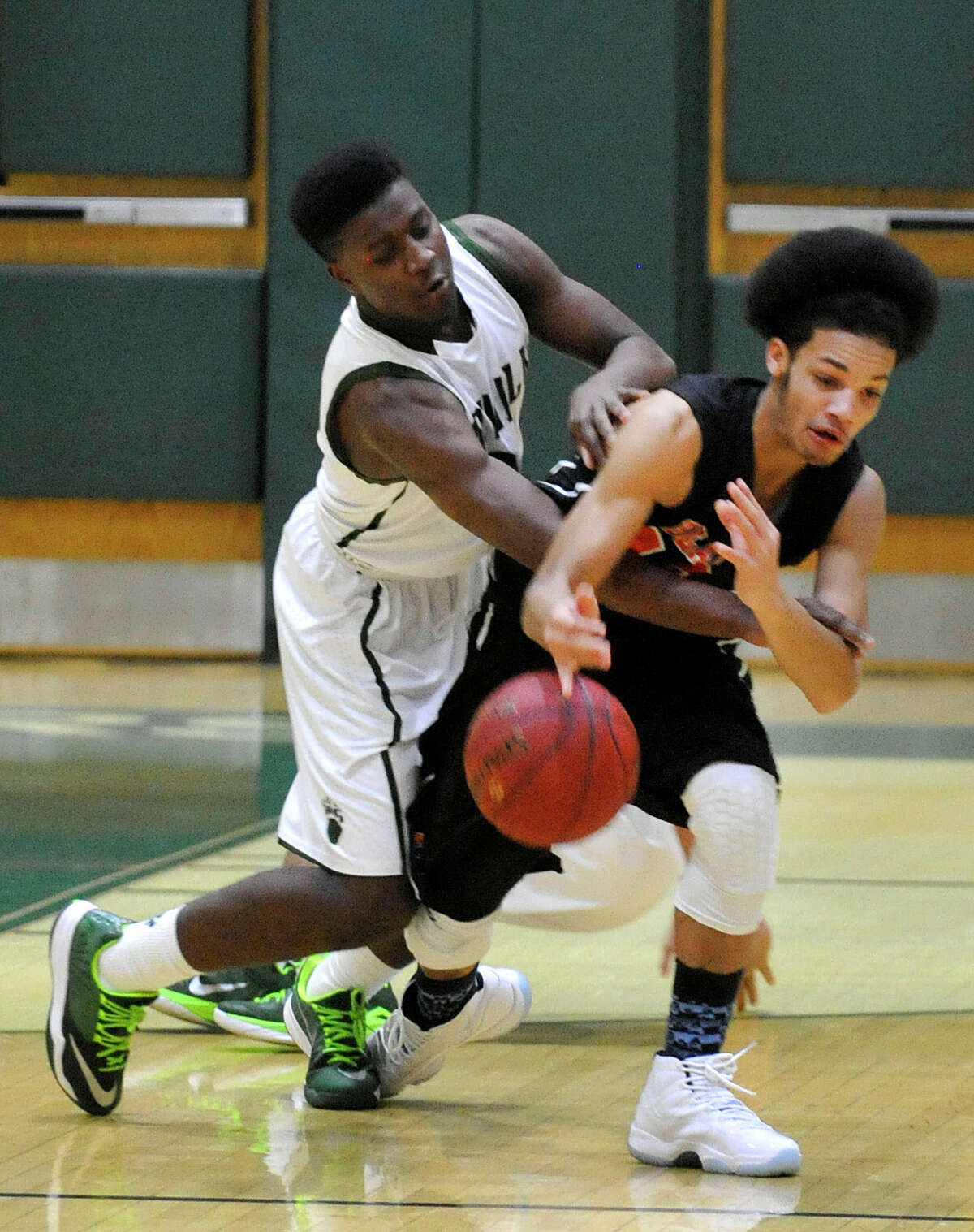 Norwalk's Bryant Bracey and Stamford's Gianni Carwin battle over the loose ball during their basketball game at Norwalk High School in Norwalk, Conn., on Tuesday, Feb. 10, 2015. Norwalk won, 56-51.