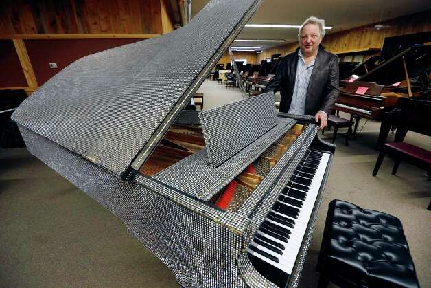In this Saturday, Jan. 24, 2015 photo, Rob Norris, owner of the Piano Mill in Rockland, Mass., stands beside a piano once owned by Liberace. A section of roof collapsed into the music store's showroom under the weight of snow Tuesday, Feb. 10, 2015, after Rockland received 29 inches of new snow the previous day. Norris said it is unclear if the Liberace piano was damaged. No one was in the building at the time of the collapse, nor is anyone being allowed inside until a structural engineer assesses damage. (AP Photo/Michael Dwyer) ORG XMIT: BX102 Photo: Michael Dwyer / AP