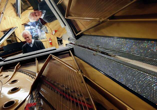 In this Saturday, Jan. 24, 2015 photo, Tim Howard, of Boston, plays a piano once owned by Liberace at the Piano Mill in Rockland, Mass. A section of roof collapsed into the music store's showroom under the weight of snow Tuesday, Feb. 10, 2015, after Rockland received 29 inches of new snow the previous day. Store owner Rob Norris said it is unclear if the Liberace piano was damaged. No one was in the building at the time of the collapse, nor is anyone being allowed inside until a structural engineer assesses damage. (AP Photo/Michael Dwyer) ORG XMIT: BX103 Photo: Michael Dwyer / AP