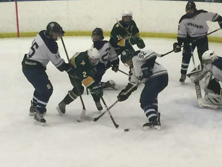 Trinity Catholic freshman Kyle Bernard, center, tries to get a shot off while surrounded by Staples defenders Robert Wehmhoff, left, and Sam Zaritsky, right during a game on Tuesday. Staples co-op won 7-1. Photo: Ryan Lacey/Staff Photo / Westport News Contributed