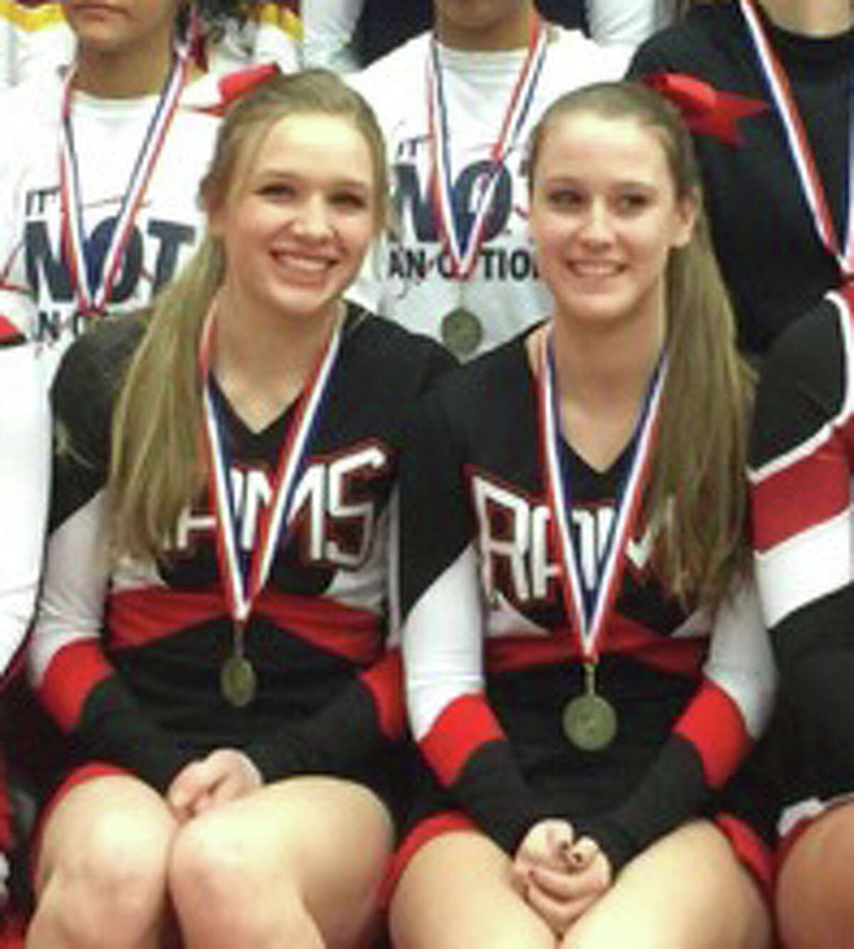Katherine Luciano (left), and Bridget Callahan pose in between all the FCIAC cheerleaders that earned All-FCIAC honors.
