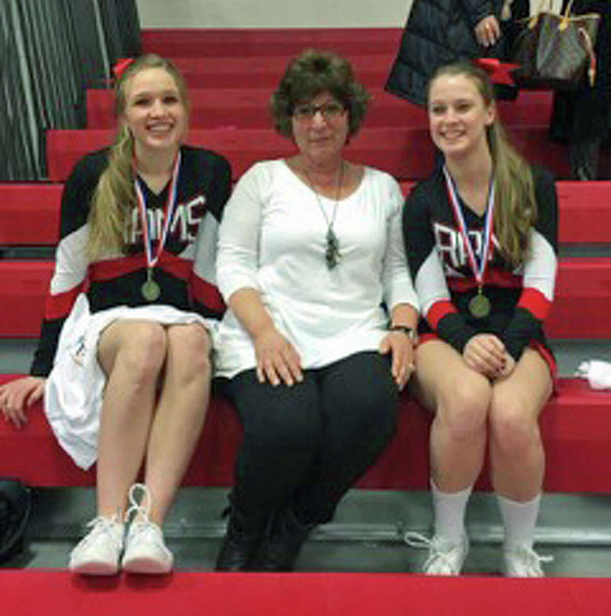 Katherine Luciano and Bridget Callahan take a picture with New Canaan cheer coach Lisa Cellini