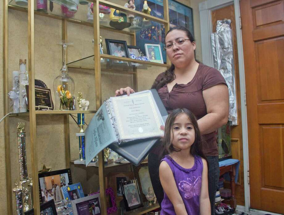 """Carmen Galvez, a Salvadoran immigrant and Houston resident, with her younger daughter Isabella, showing distinctions and honors won by her elder daughter Sofia at her high school. The Galvez family of four lives below the federal poverty level with an income of $450 a week, """"when there is work available every day,"""" she says. Gavez says her worst fear is not having money to pay college tuition for Sofia. Photo: Olivia P. Tallet, LV Staff / La Voz / Houston Chronicle"""