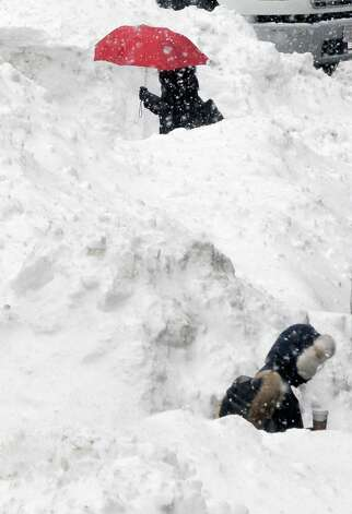 Commuters walk between piles of snow on a street in downtown Boston, Wednesday, Feb. 11, 2015. The National Weather Service forecasts a weak weather system may bring 2 to 4 inches of new snow Thursday into Friday morning to the region, which already has seen record snowfalls this winter. (AP Photo/Bill Sikes) ORG XMIT: BX101 Photo: Bill Sikes, AP / AP