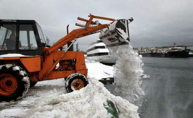 In this photo taken Tuesday, Feb. 10, 2015, snow is dumped in to Gloucester Harbor after being cleared from Cruiseport Gloucester parking lot in Gloucester, Mass,. Just as southern New England residents have finished digging out from the latest storm, forecasters say more snow is on the way.  (AP Photo/The Boston Globe, Jimmy O'Neill)  BOSTON HERALD OUT, QUINCY OUT; NO SALES Photo/John Blanding, Boston Globe staff   story/, Met ( feature )       ORG XMIT: MABOD201 Photo: John Blanding, AP / The Boston Globe