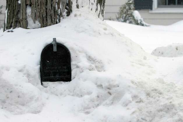A mailbox sits in a pile of snow Wednesday, Feb. 11, 2015 in Weston, Mass. The National Weather forecasts a weak weather system that may bring 2 to 4 inches of new snow Thursday into Friday morning to the region, which already has seen record snowfalls this winter. (AP Photo/Bill Sikes) ORG XMIT: BX102 Photo: Bill Sikes, AP / AP