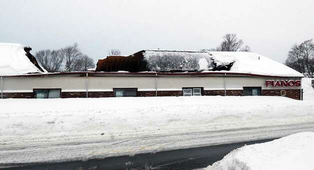 The roof of the Piano Mill sits partially collapsed into the music store's showroom from the weight of snow, Tuesday, Feb. 10, 2015, after 29 inches of new snow fell in Rockland, Mass. The store is home to a rhinestone-covered grand piano once owned by Liberace. Store owner Rob Norris said it is unclear if the Liberace piano was damaged. No one was in the building at the time of the collapse, nor was anyone being allowed inside until a structural engineer assesses damage. (AP Photo/The Brockton Enterprise, Marc Vasconcellos)  ORG XMIT: MABRO102 Photo: Marc Vasconcellos, AP / The Enterprise