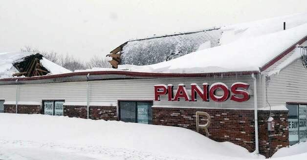 The roof of the Piano Mill sits partially collapsed into the music store's showroom from the weight of snow, Tuesday, Feb. 10, 2015, after 29 inches of new snow fell in Rockland, Mass. The store is home to a rhinestone-covered grand piano once owned by Liberace. Store owner Rob Norris said it is unclear if the Liberace piano was damaged. No one was in the building at the time of the collapse, nor was anyone being allowed inside until a structural engineer assesses damage. (AP Photo/The Brockton Enterprise, Marc Vasconcellos)  ORG XMIT: MABRO101 Photo: Marc Vasconcellos, AP / The Enterprise