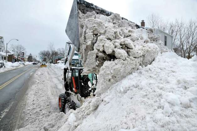 A worker uses a compact front-end loader to pile snow from a road to be removed by a dump truck near Davis Square in Somerville, Mass., Tuesday, Feb. 10, 2015. The third major winter storm in two weeks left the Boston area with another two feet of snow and forced the MBTA to suspend all rail service for the day. (AP Photo/Josh Reynolds) ORG XMIT: MACR110 Photo: Josh Reynolds, AP / FR25426 AP