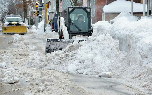 A worker uses a compact front-end loader to clear snow from a road to be removed by a dump truck near Davis Square in Somerville, Mass., Tuesday, Feb. 10, 2015. The third major winter storm in two weeks left the Boston area with another two feet of snow and forced the MBTA to suspend all rail service for the day. (AP Photo/Josh Reynolds) ORG XMIT: MACR112 Photo: Josh Reynolds, AP / FR25426 AP