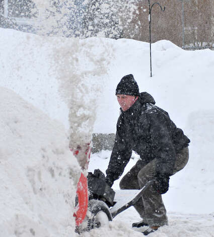 Dave Wason of Attleboro, Mass. helps a neighbor clear her driveway during another winter snow storm Monday, Feb. 9, 2015. Winter weary Massachusetts residents lamented another snowstorm that was expected to leave close to two feet of additional snow in some areas of the state, as public officials tried to figure out how they were going to pay for removal, where to put it all, and how to make up lost school days. (AP Photo/The Sun Chronicle, Mark Stockwell) ORG XMIT: MAATT102 Photo: Mark Stockwell, AP / The Sun Chronicle