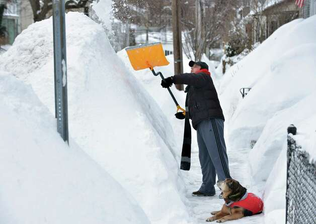 Lee Anderson adds to the pile of snow beside the sidewalk in front of his house in Somerville, Mass., Tuesday, Feb. 10, 2015, as his dog Ace looks on. The latest snowstorm left the Bostonarea with another two feet of snow and forced the MBTA to suspend all rail service for the day. (AP Photo/Josh Reynolds) ORG XMIT: MACR101 Photo: Josh Reynolds, AP / FR25426 AP
