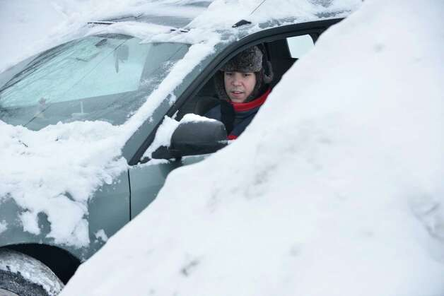 Will Chapman, of Oakland, Calif., works to free his car from between snow piles near the house he was visiting in Somerville, Mass., Tuesday, Feb. 10, 2015. The latest snowstorm left the Boston area with another two feet of snow and forced the MBTA to suspend all rail service for the day. (AP Photo/Josh Reynolds) ORG XMIT: MACR103 Photo: Josh Reynolds, AP / FR25426 AP