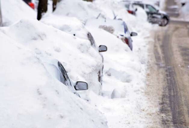 A line of cars sit buried in snow banks in Somerville, Mass., Tuesday, Feb. 10, 2015. The latest snowstorm left the Boston area with another two feet of snow and forced the MBTA to suspend all rail service for the day. (AP Photo/Josh Reynolds) ORG XMIT: MACR104 Photo: Josh Reynolds, AP / FR25426 AP