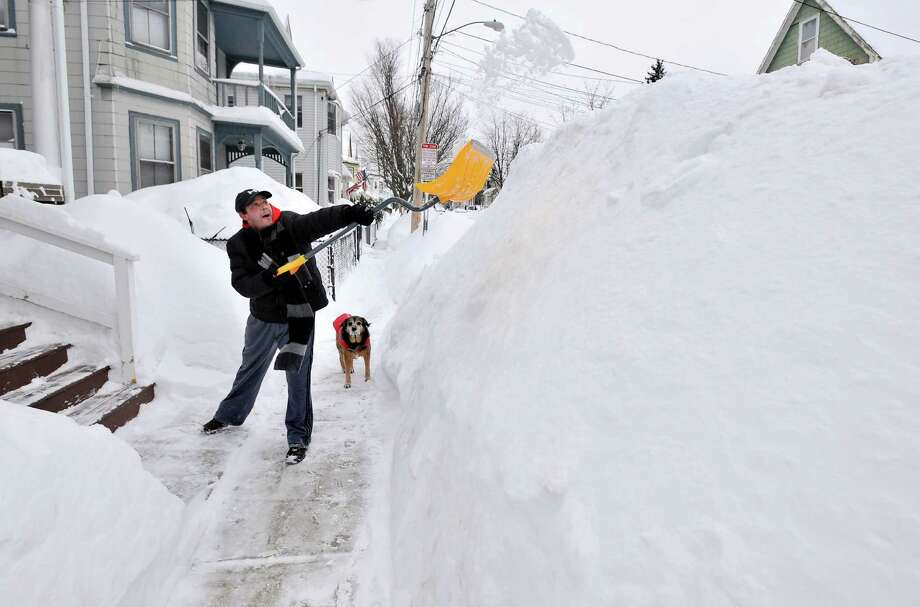 Lee Anderson adds to the pile of snow beside the sidewalk in front of his house in Somerville, Mass., Tuesday, Feb. 10, 2015, as his dog Ace looks on. The latest snowstorm left the Boston area with another two feet of snow and forced the MBTA to suspend all rail service for the day. (AP Photo/Josh Reynolds) ORG XMIT: MACR106 Photo: Josh Reynolds, AP / FR25426 AP