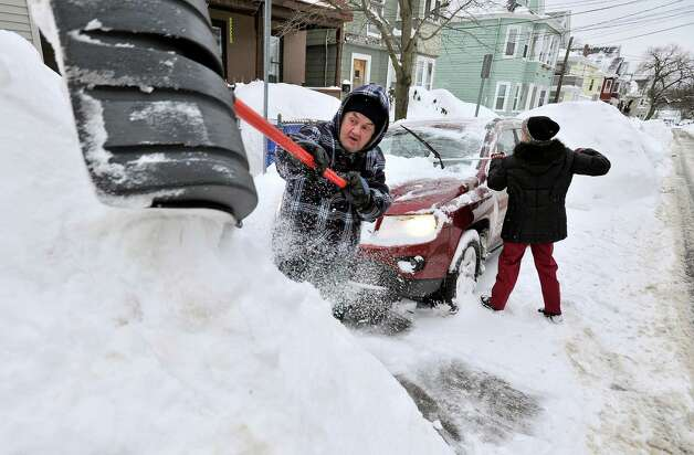 Rich and Kathy Melvin shovel out their car in front of their house in Somerville,, Mass., Tuesday, Feb. 10, 2015. The latest snowstorm left the Boston area with another two feet of snow and forced the MBTA to suspend all rail service for the day. (AP Photo/Josh Reynolds) ORG XMIT: MACR107 Photo: Josh Reynolds, AP / FR25426 AP