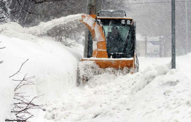 City worker Jeff D'Amico clears snow from a sidewalk, Monday, Feb. 9, 2015, in Marlborough, Mass. New England and portions of New York state awoke Monday to a fresh blanket of snow as a storm threatening to bring up to 1 to 2 feet to some areas churned across the Northeast, making for a slippery, tedious commute to start the workweek. (AP Photo/Bill Sikes) ORG XMIT: MAWS108 Photo: Bill Sikes, AP / AP