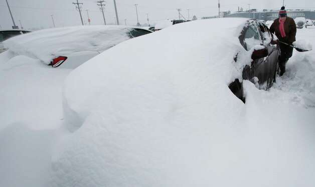 Mary Mulloy of Strafford, Vt., works to dig her car out of the long term parking lot at the Manchester-Boston Regional Airport Monday, Feb. 9, 2015, in Manchester, N.H.  Mulloy was returning from Salt Lake City, where temperatures were in the 70s. (AP Photo/Jim Cole) ORG XMIT: NHJC102 Photo: Jim Cole, AP / AP