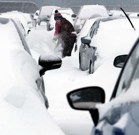 Mary Mulloy, of Strafford, Vt., works to dig her car out of the long term parking lot at the airport, Monday, Feb. 9, 2015, in Manchester, N.H. Mulloy was returning from Salt Lake City, where temperatures were in the 70s. (AP Photo/Jim Cole) ORG XMIT: NHJC101 Photo: Jim Cole, AP / AP