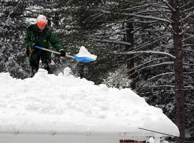 Bjorn Lange works to shovel off his roof as another snowstorm hits the area Monday, Feb. 9, 2015, in Concord, N.H. More light, fluffy snow was falling in much of New Hampshire on Monday, the latest in a series of storms piling it on this winter. (AP Photo/Jim Cole) ORG XMIT: NHJC103 Photo: Jim Cole, AP / AP