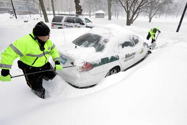 Boston park rangers clear snow from around their car Monday, Feb. 9, 2015, on Boston Common. A long duration winter storm that began Saturday night remains in effect for a large swath of southern New England until the early morning hours Tuesday. (AP Photo/Steven Senne) ORG XMIT: BX101 Photo: Steven Senne, AP / AP