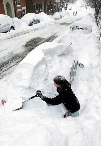 Taylor LaBrecque digs her car out of a snow pile on Beacon Hill Monday, Feb. 9, 2015, in Boston. A long duration winter storm that began Saturday night remains in effect for a large swath of southern New England until the early morning hours Tuesday. (AP Photo/Steven Senne) ORG XMIT: BX102 Photo: Steven Senne, AP / AP