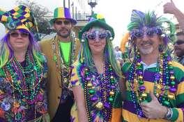 Juerguistas celebran Mardi Gras en el histórico Distrito Strand de Galveston el sábado 7 de febrero de 2015.