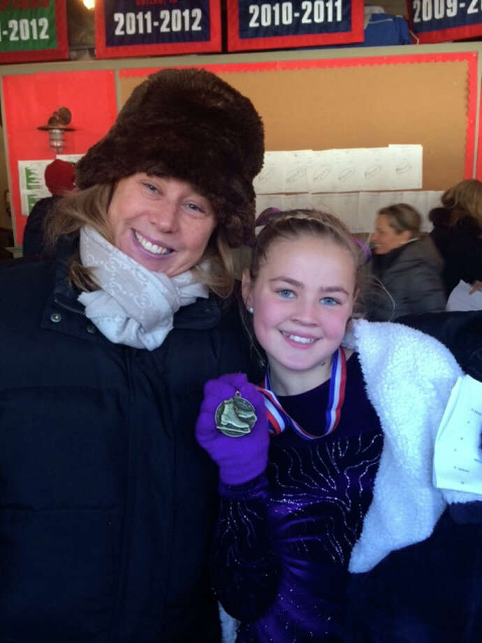 Cate Hicks and her coach Kelly Feda celebrate her gold medal victory in the Basic 3 level competition. Cate is an 11 year-old resident of Greenwich and member of the Greenwich Skating Club. Photo: Contirbuted, Contributed / Darien News