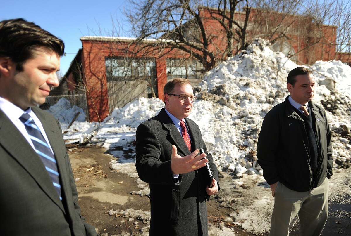 From left; Deputy Commissioner for the Department of Economic and Community Development Tim Sullivan, Stratford Mayor John Harkins, and town Conservation Administrator Brian Carey announce the start of the demolition and remediation of the Contract Plating site at 540 Longbrook Avenue in Stratford, Conn. on Wednesday, February 11, 2015. The work is being funded with a $2.85 million grant from the state Department of Economic Development.