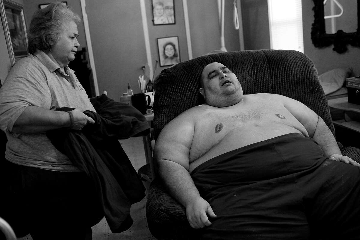 """Hector Garcia Jr. rests in his chair after returning from the bathroom with the help of his mother, Elena Garcia, left, at their home in November 2010. """"Obesity is horrible. It's like being in a prison. It's like being in prison and the prison is your own body,"""" Garcia said."""