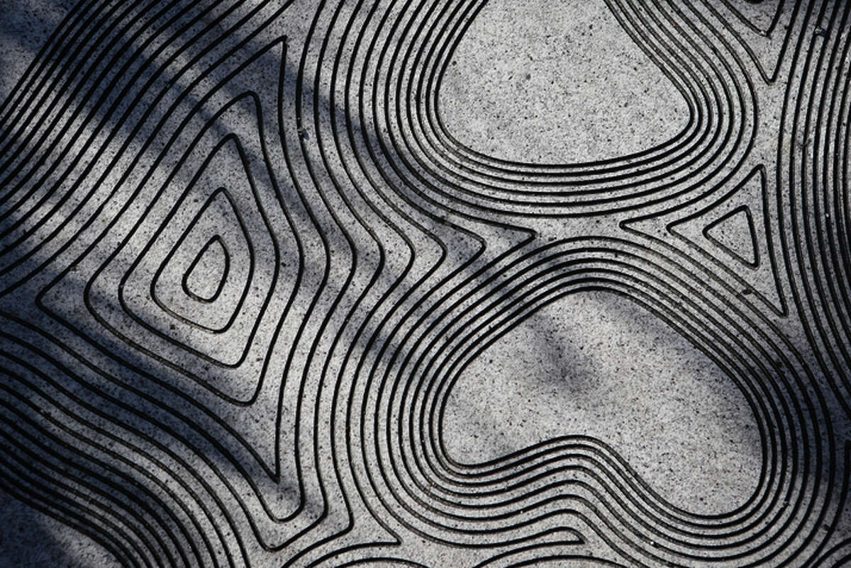 """Abstract maps are engraved on the granite walking path of Mid-Market's """"Promised Land."""""""